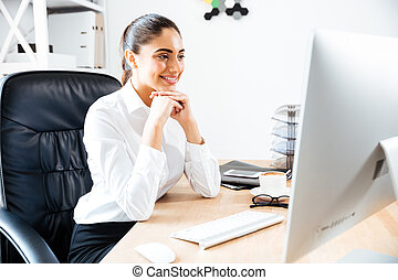 Happy young businesswoman looking at computer screen while...
