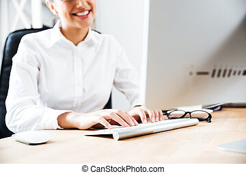 Cropped image of a smiling happy businesswoman typing on...