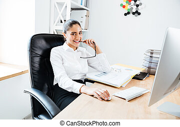 Happy yong businesswoman sitting at her workplace holding...