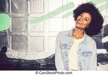 Portrait of a young black woman, model of fashion in urban...