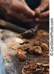 cracking almonds with a hammer - closeup of a pile of...