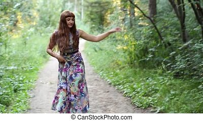 Happy girl dancing and smiling on a path in the woods
