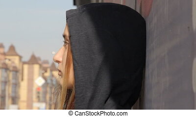 A teenager girl in a hoody with the hood on and loose...
