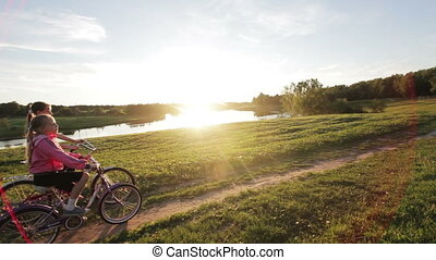 Girls riding bicycle in the countryside - Young girls riding...