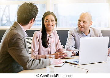 Three business executives communicating during meeting in...