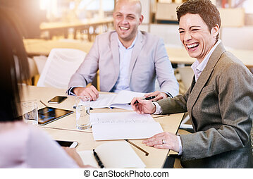 Businesswoman and businessman laughing happily towards...