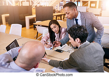 Businessman supervising his employees as they brainstorm and...