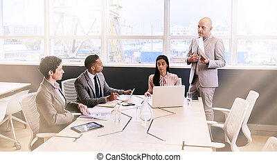 Businessman giving a presentation to colleagues in...