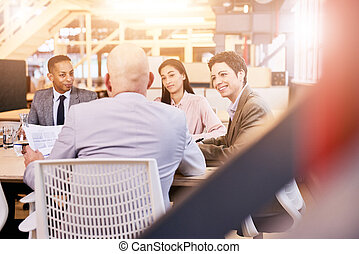 Business meeting indoors in colourful modern office space -...