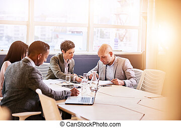 Business meeting between four professional executives in...