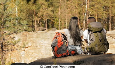 Hiking couple sits on the edge of the cliff
