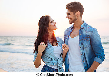 Couple standing and looking at each other on the beach