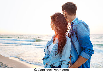 Couple looking at sunrise on the beach