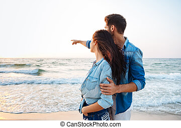 Couple standing and pointing away on the beach - Beautiful...