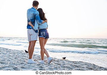 Back view of young couple enjoying sunrise on the beach