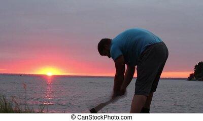 tourist chopping tree at sunset