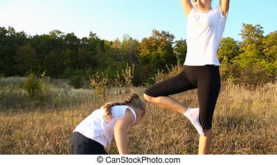 Mom and daughter doing yoga