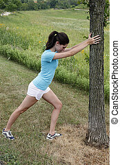 Young woman stretching on a tree
