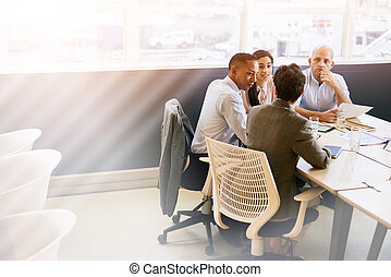Four eclectic business individuals conducting a meeting in...