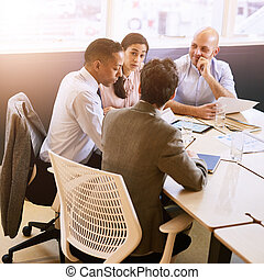 Four business professionals in a meeting indoors - Square...