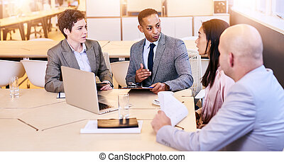 Eclectic group of four business professionals conducting a...