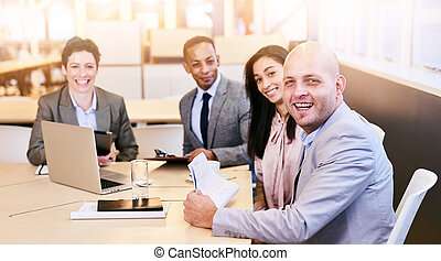 four business professionals looking at the camera during a...