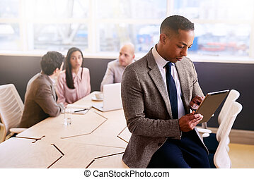 Businessman using a tablet with three colleagues seated behind him
