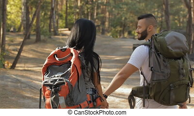 Couple of hikers continues the walking at the forest -...