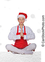 chef in hat of Santa doing yoga with snow on white...