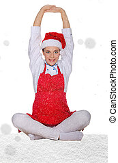 beautiful cook in Santa Claus hat with snow on white...