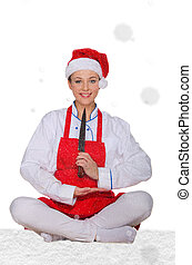 Cook in Santa Claus hat, yoga, knife under snow on white...