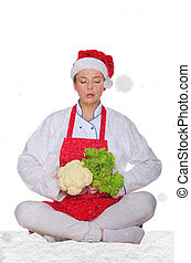 chef in hat of Santa Claus, yoga, vegetables under snow on...