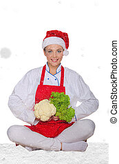 chef in hat of Santa, yoga, vegetables under snow on white...
