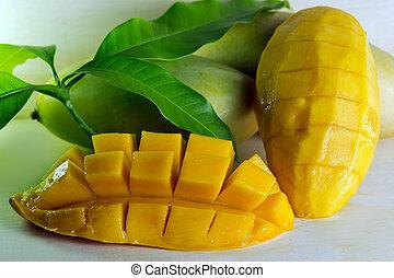 Mango nicely cut with leaf on wooden background (Also known as horse mango, Mangifera foetida, Anacardiaceae, Mangifera, M. indica)