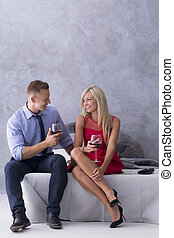 Would you mind a glass of wine? - Couple sitting on a bed...