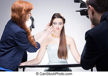 Taking care of all the details - Shot of a make-up girl...