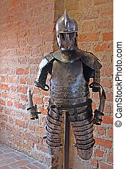 Knight armour - Suit of medieval armour in front of brick...