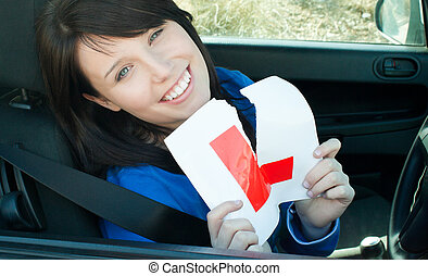 Cheerful young female driver tearing up her L sign sitting...