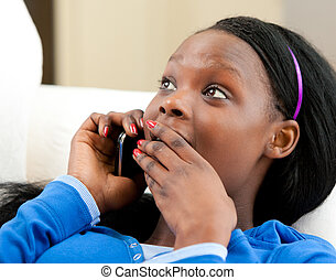 Astonished afro-american teenager talking on phone lying on...