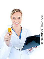 Smiling young doctor holding a laptop and pills against...