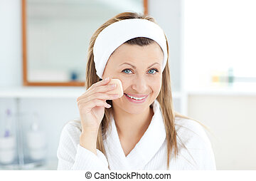Radiant woman putting cream on her face in the bathroom