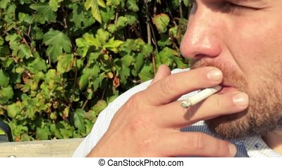 man smokes on the bench in the park - man smokes a cigarette...