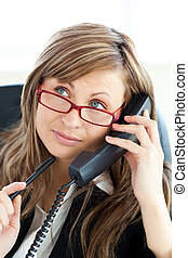 Pensive businesswoman talking on phone wearing glasses...