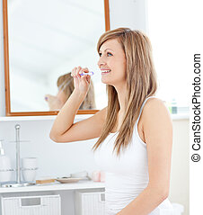 Blond young woman brush her teeth
