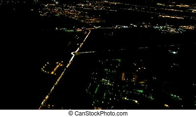 City lights at night from descending aircraft in flight...