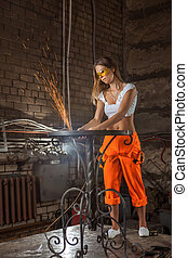 Mechanic woman in sexy uniform is working with the sander.