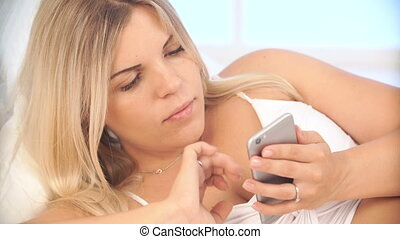 Pregnant woman using smart phone at home lying on bed -...