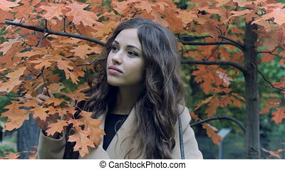 Beautiful model posing for photos in the park in autumn