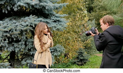 Photographer photographing model among the trees in the park.