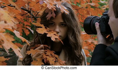 Photographer photographing model among the trees in the park, slow motion